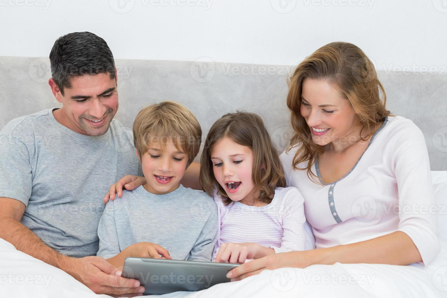 familj som använder den digitala surfplattan i sängen foto