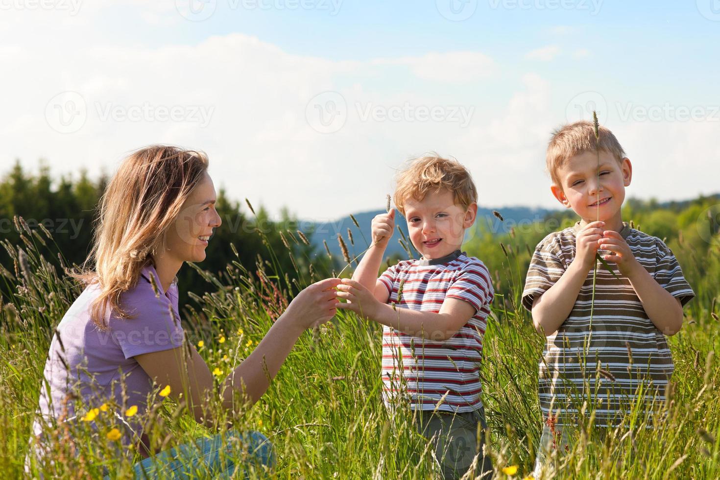 familj sommar - spelar på ängen foto