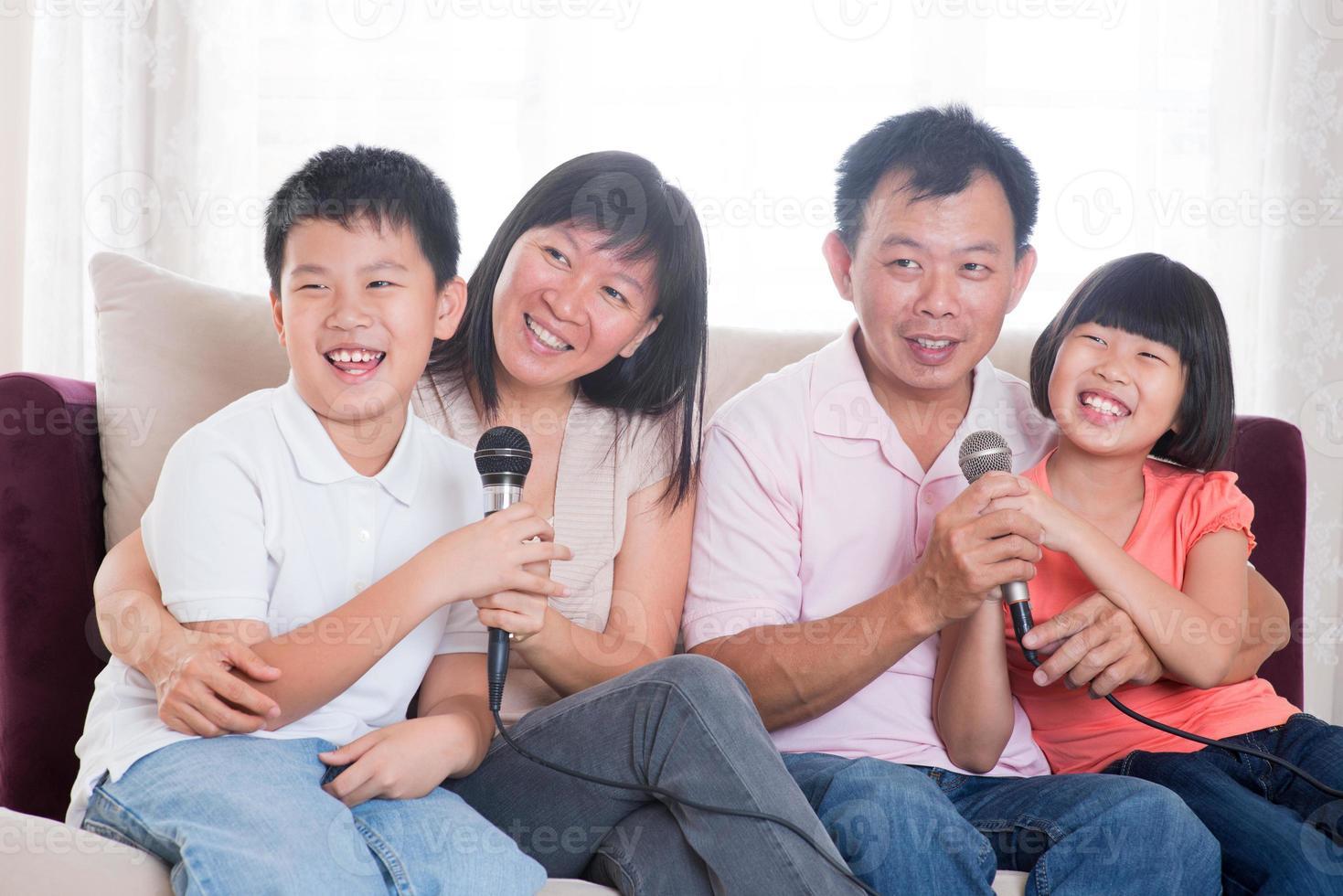 asiatisk familj med fyra sjungande karaoke foto