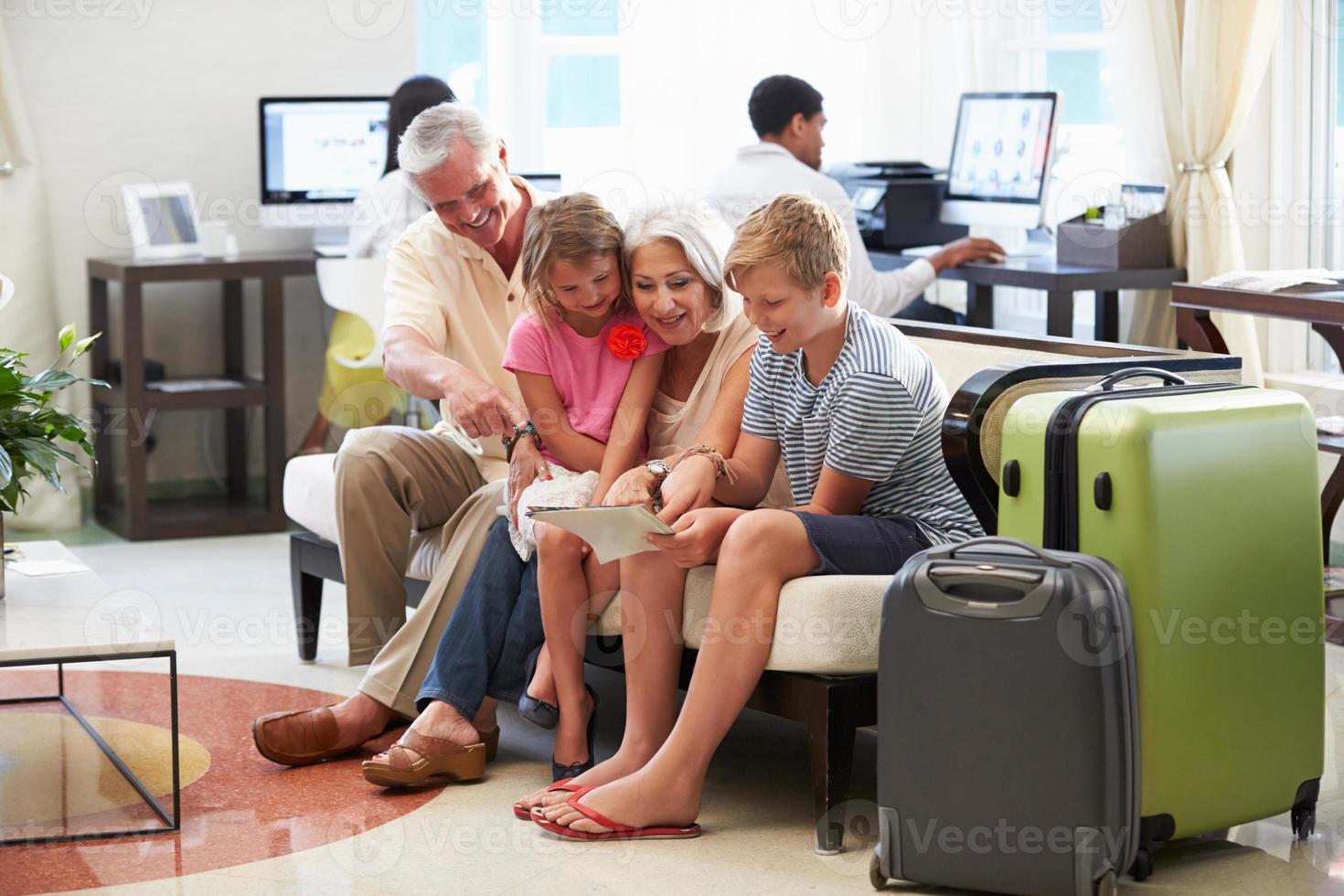morföräldrar med barnbarn som anländer till hotelllobbyen foto