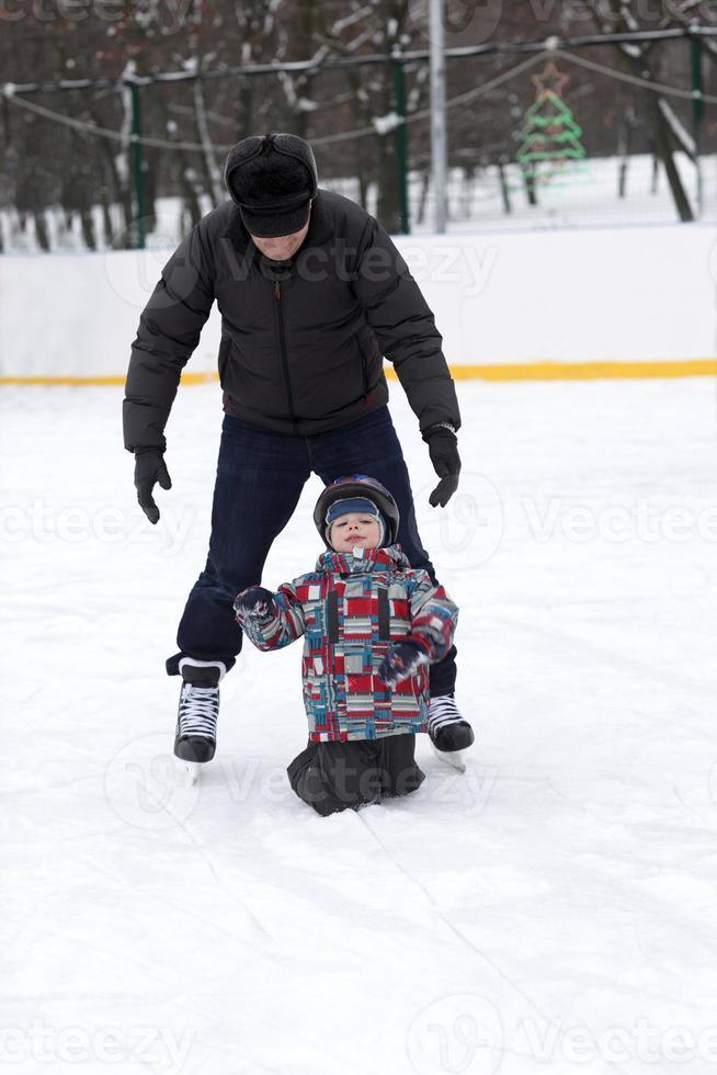 farfar lär sitt barnbarn att åka skridskor foto