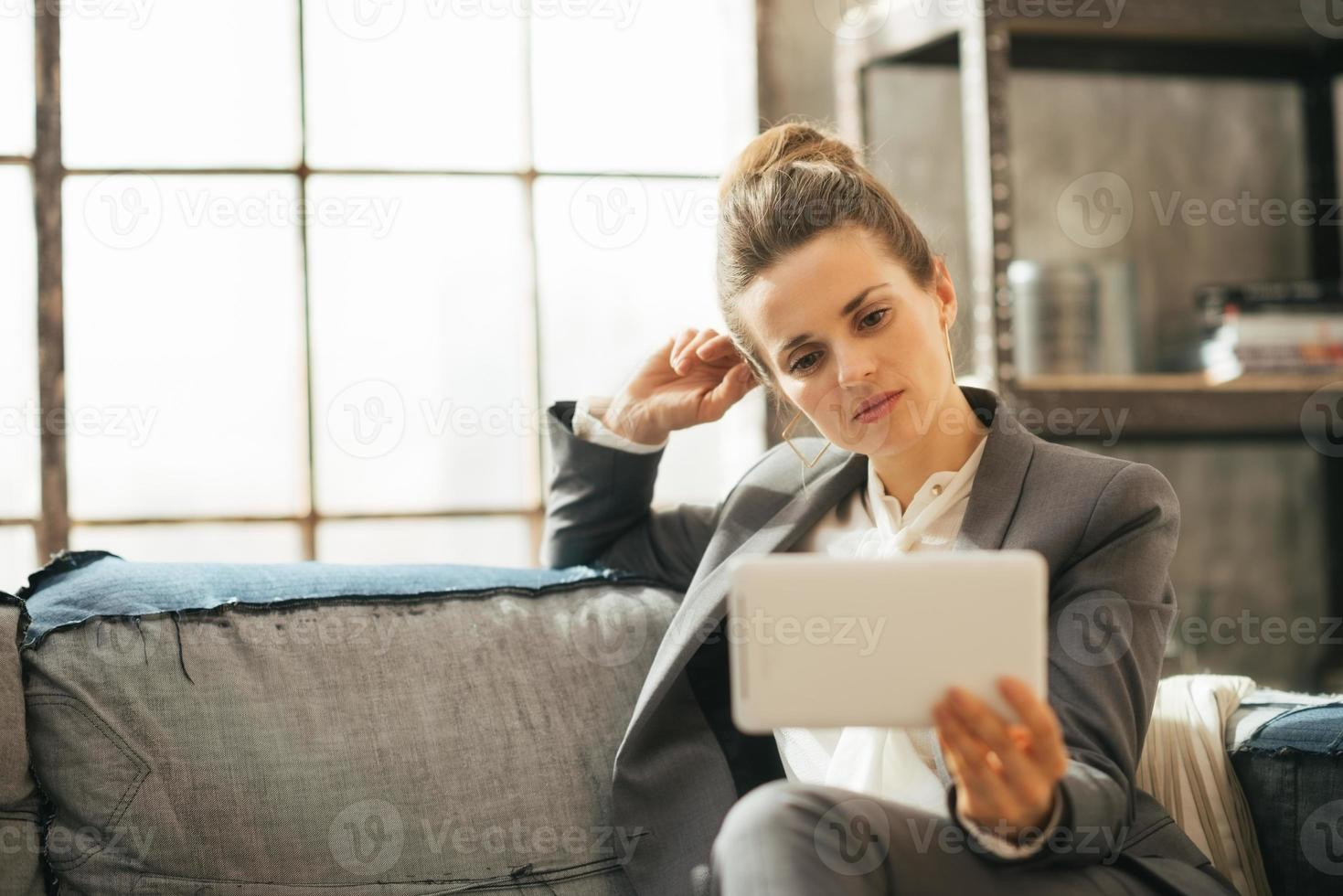 tankeväckande affärskvinna som använder TabletPC i loftlägenhet foto