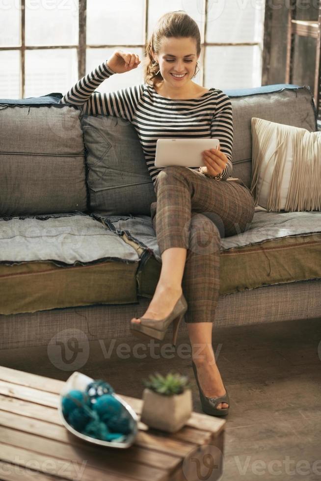 glad ung kvinna som använder tablet pc i loftlägenhet foto