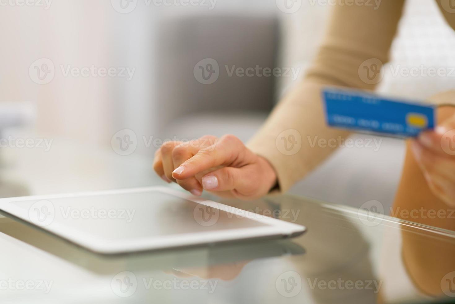 närbild på ung kvinna med kreditkort med hjälp av TabletPC foto