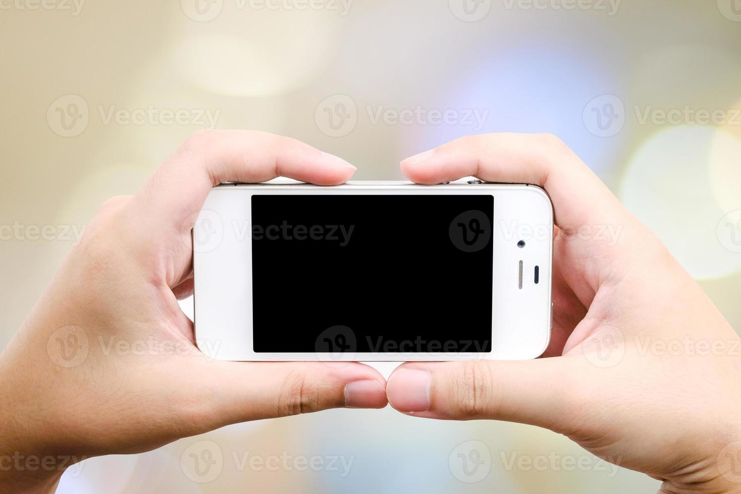 smart telefon i handen på bokeh bakgrund foto