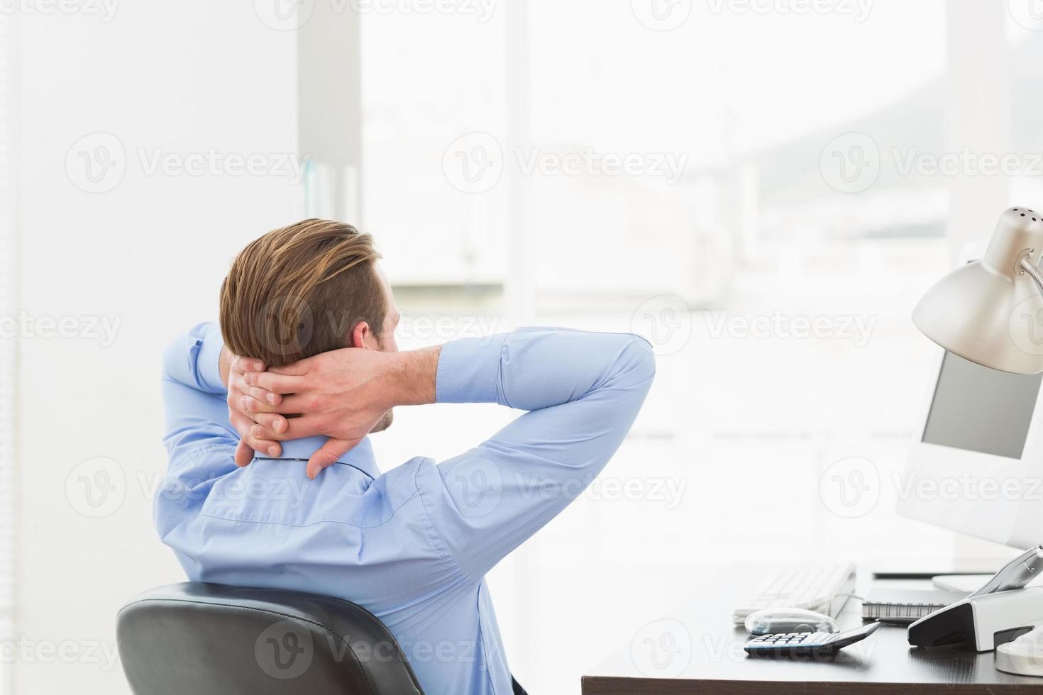 affärsman kopplar av i en svängbar stol lutad tillbaka foto