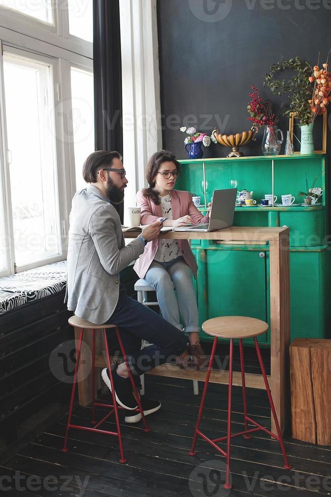 modernt team som arbetar i café med bärbar dator, smartphone med kaffe foto