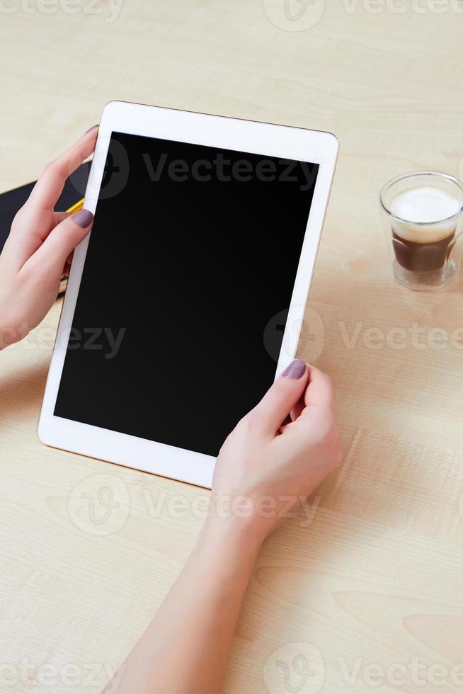 håller en vit digital tablet på jobbet foto