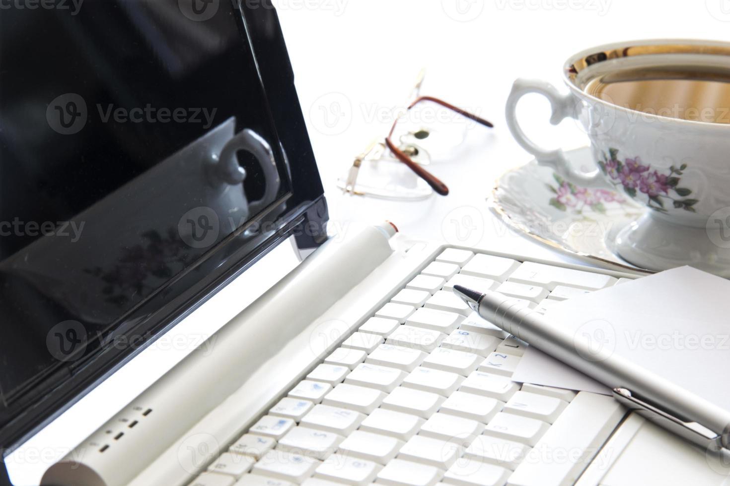 bärbar dator och kopp kaffe på kontoret foto