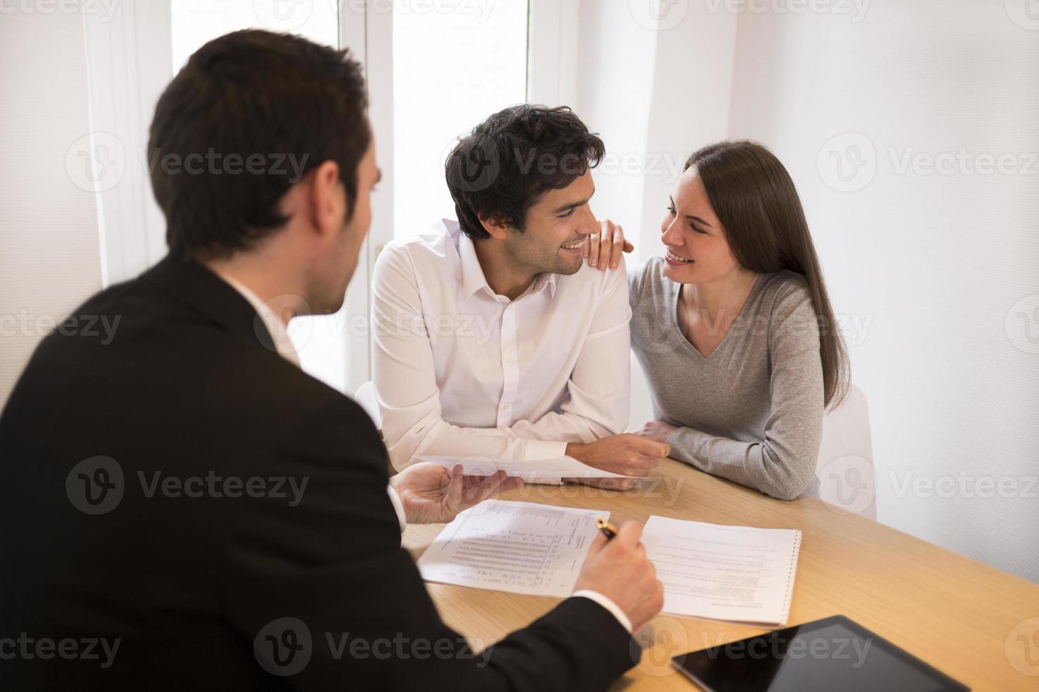 ungt par möter fastighetsmäklare för att köpa fastighet, presentationsbräda foto
