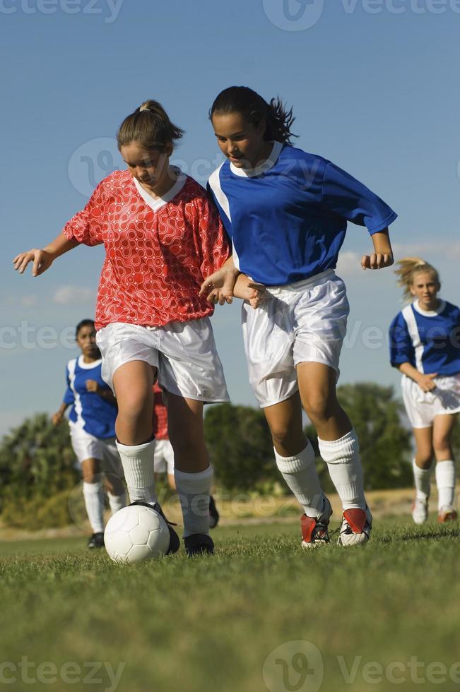 tonårsflickor som spelar fotboll foto