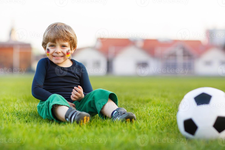 blond pojke på 4 som spelar fotboll med fotbollsplanen foto