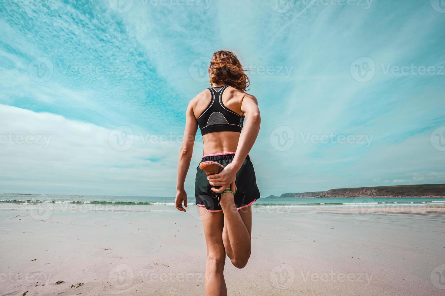 atletisk ung kvinna som sträcker sig på stranden foto