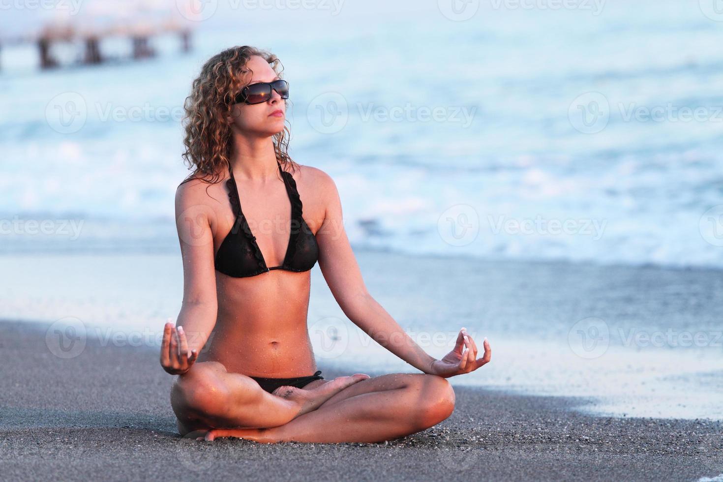 kropp av vacker flicka i meditation på stranden. lotus position foto