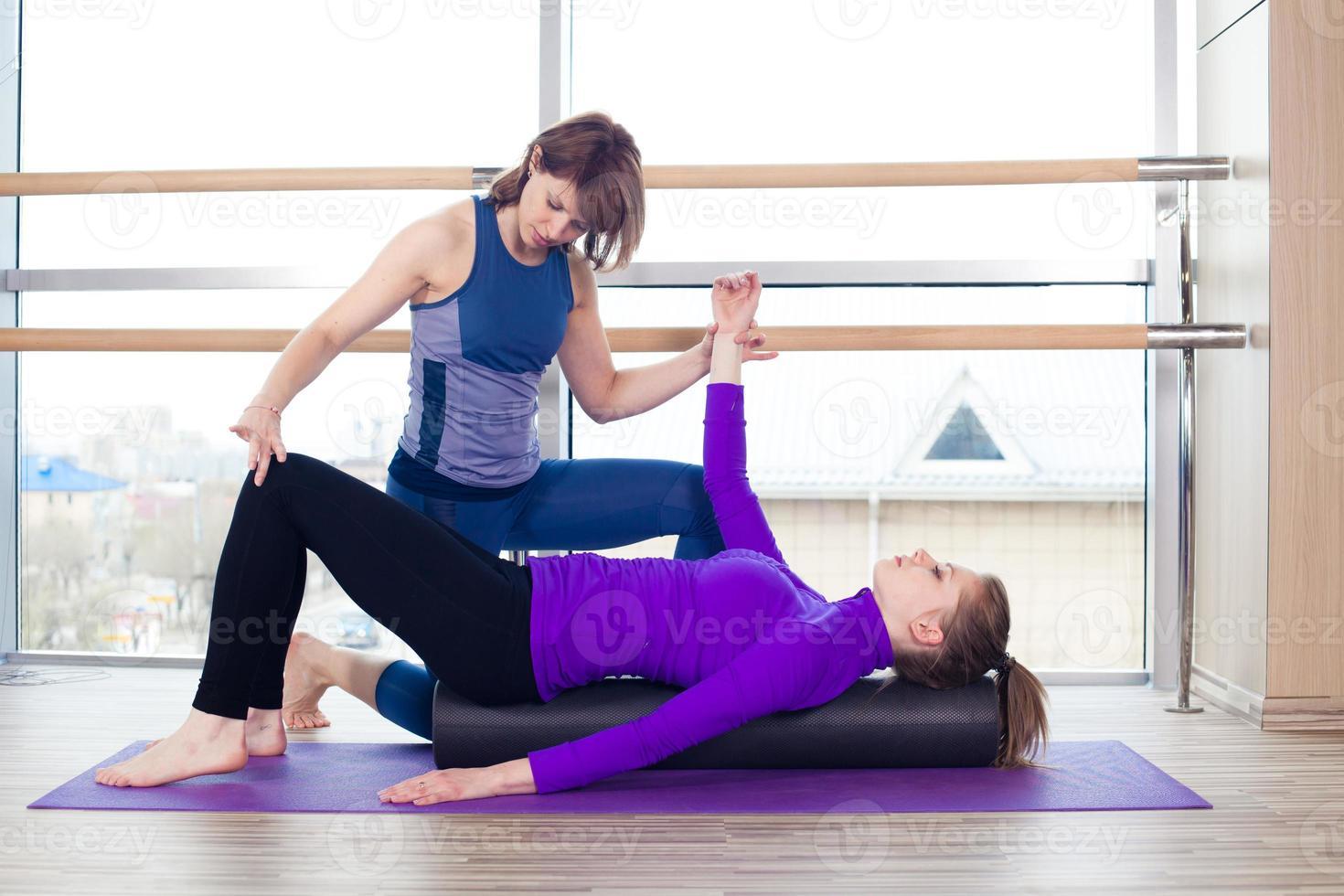 aerobics pilates personlig tränare som hjälper kvinnor att gruppera i ett gym foto