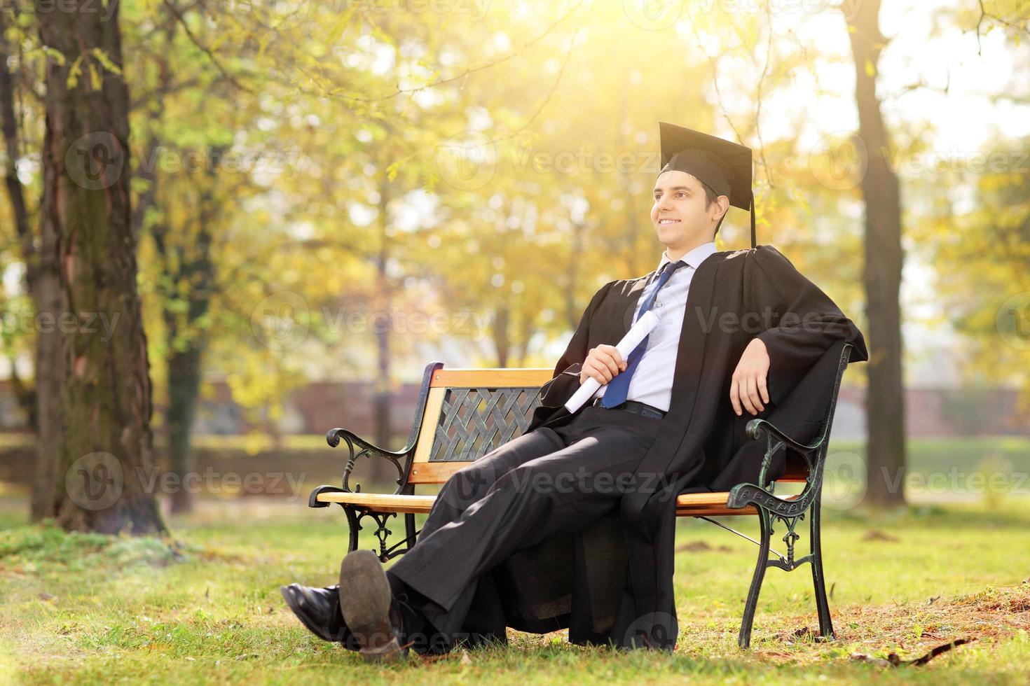 högskoleexamen njuter i parken foto