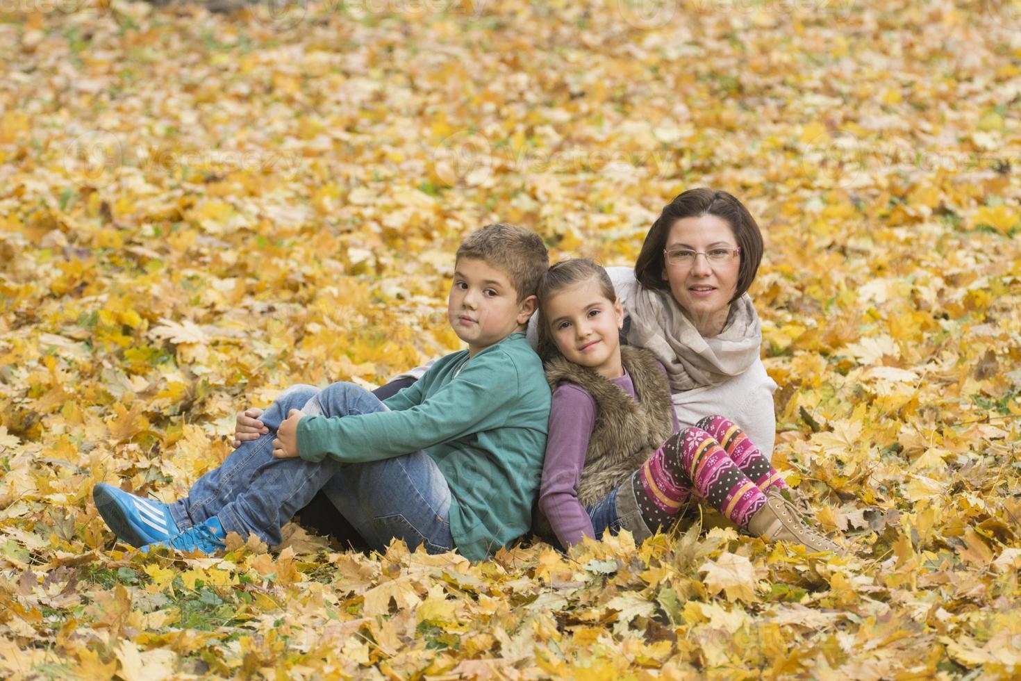 mor och barn njuter av hösten i parken foto
