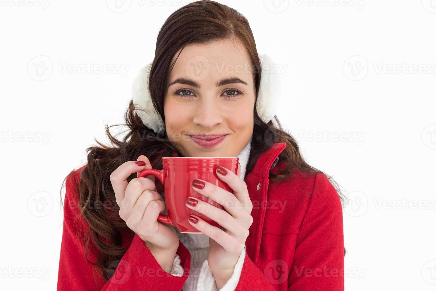 kvinna i vinterkläder njuter av en varm drink foto