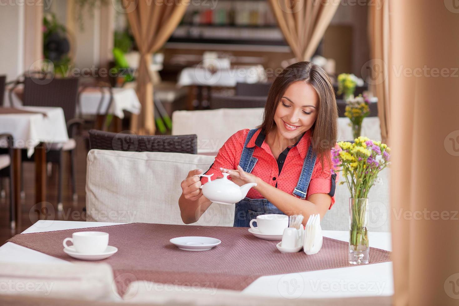 vacker hipster tjej njuter av varm dryck på café foto