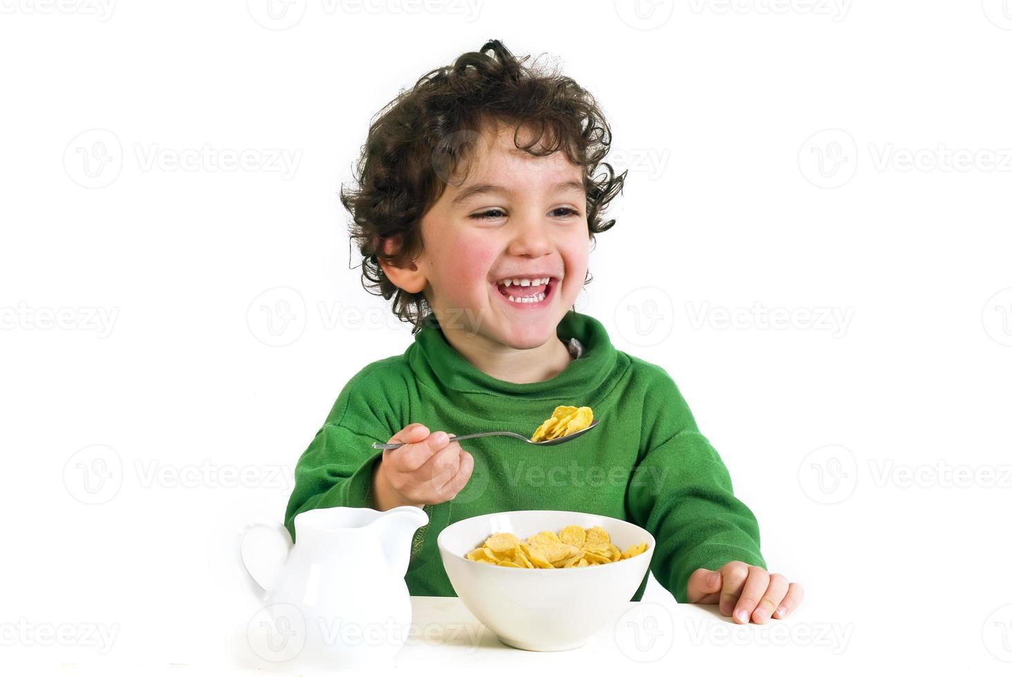 ung pojke skrattar, njuter av sitt morgon spannmål med mjölk foto