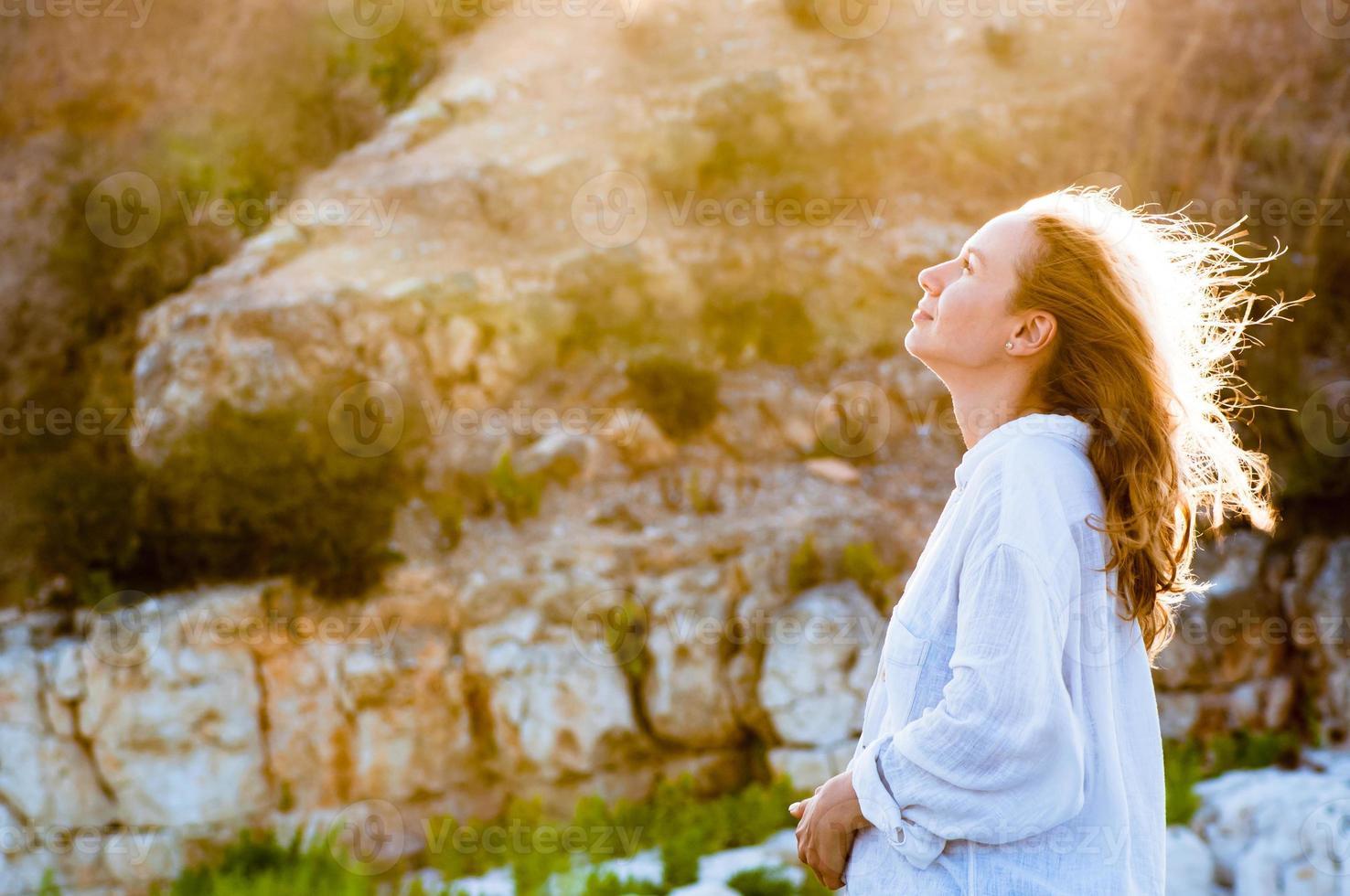 vacker ung kvinna i vit skjorta njuter av solnedgången ljus foto