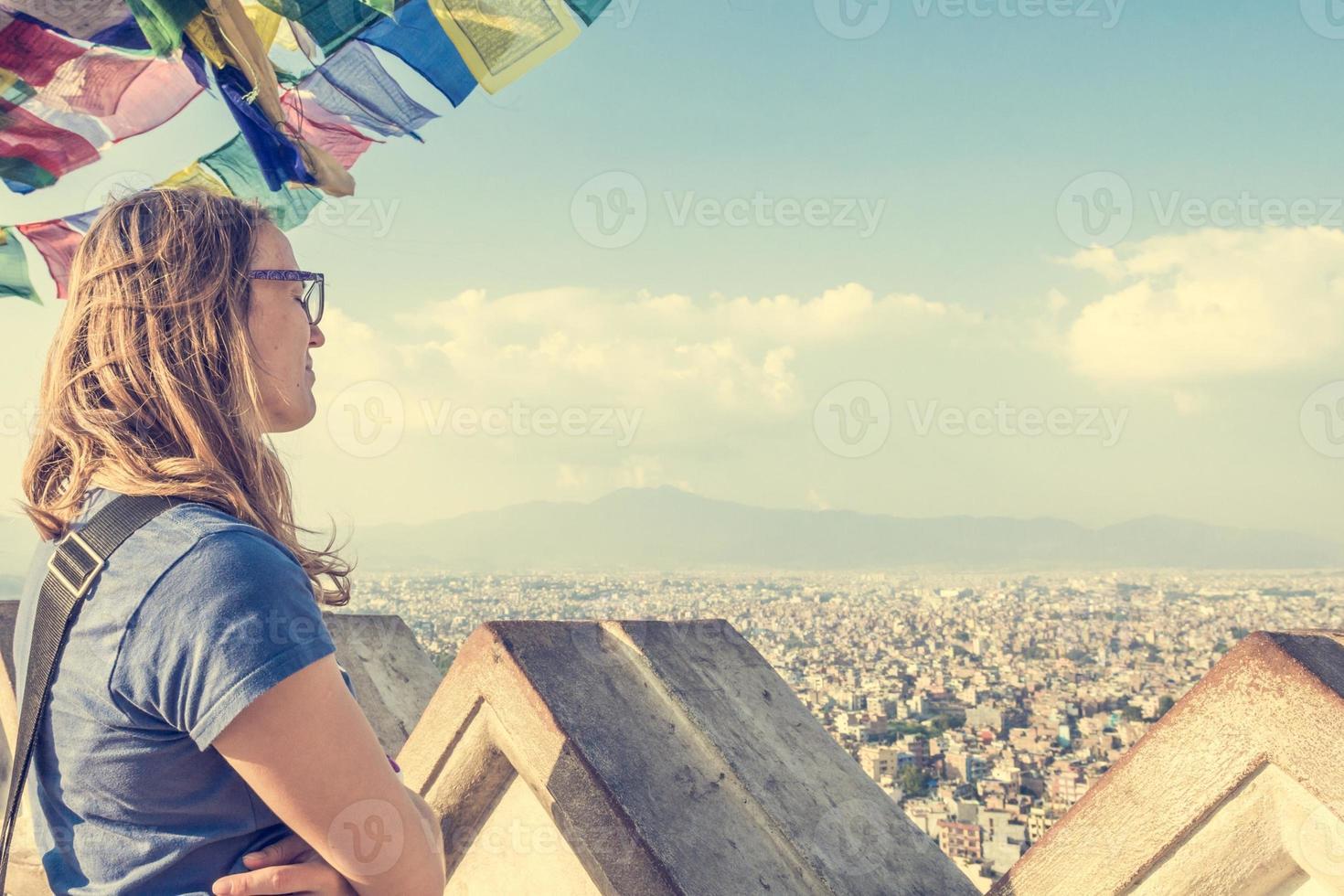 ung kvinna njuter av kvällen utsikt över en stad. foto