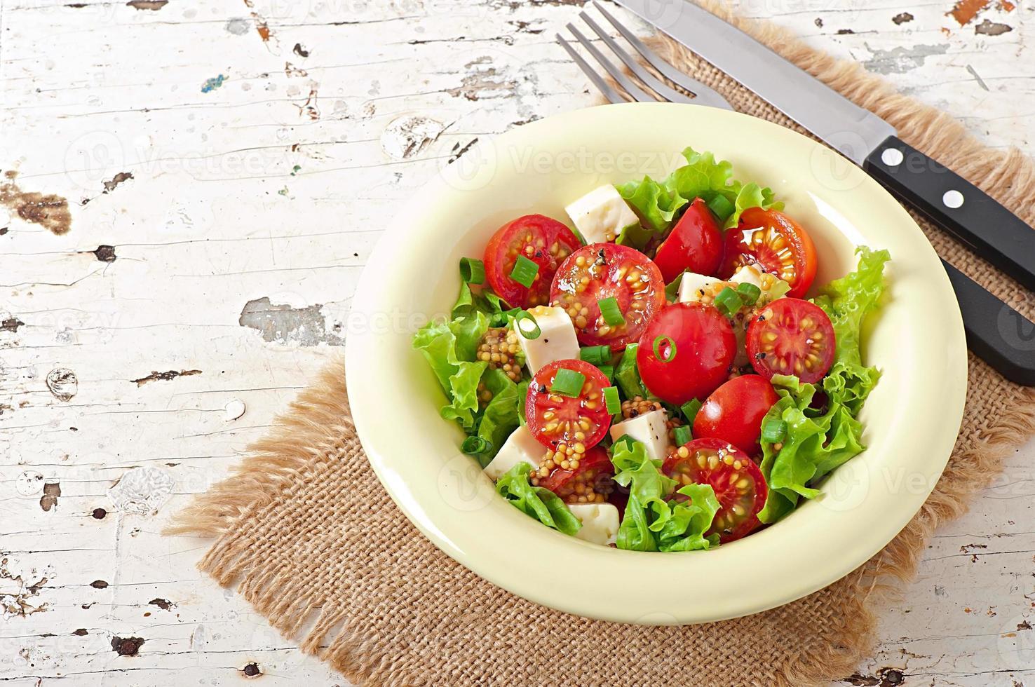 tomatsallad med sallad, ost och senap och vitlökdressing foto
