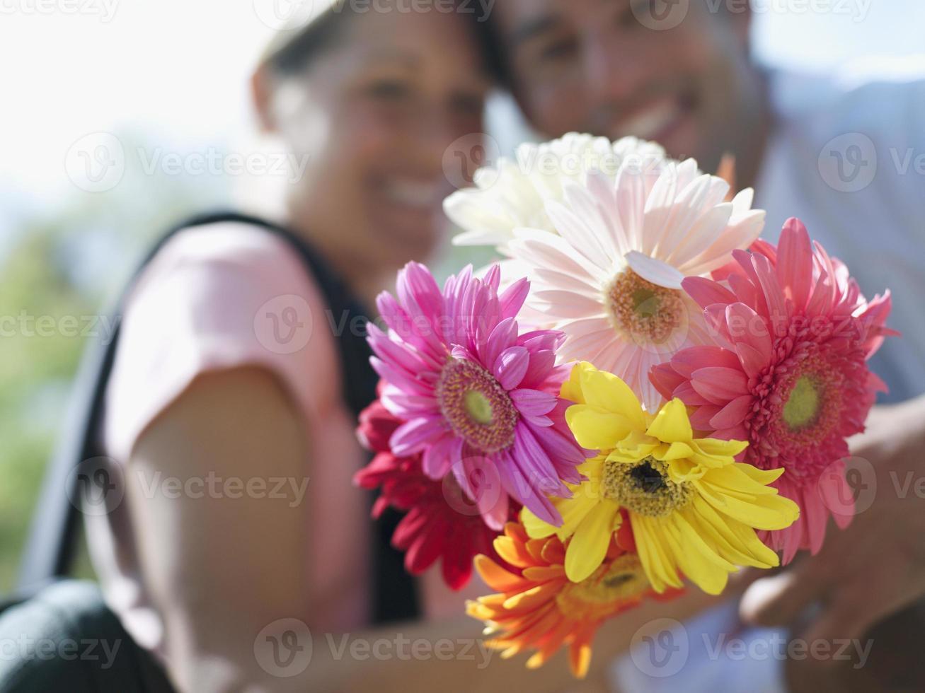 par som håller gäng färgglada blommor, närbild, fokus på fo foto