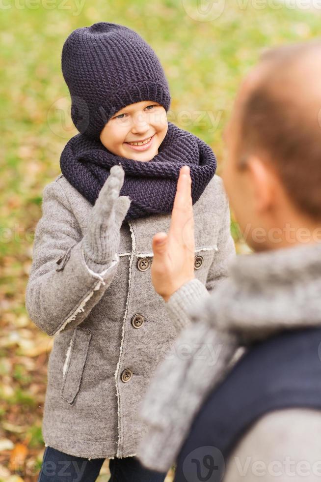 lycklig far och son som gör high five i park foto