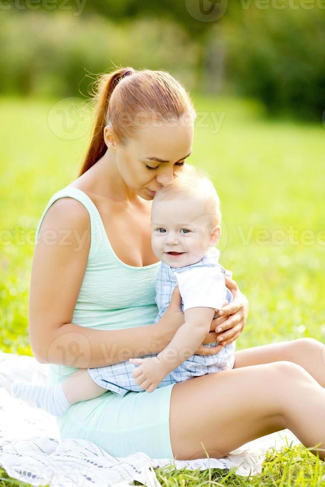 söt liten baby i sommarparken med mamma på gräset. foto
