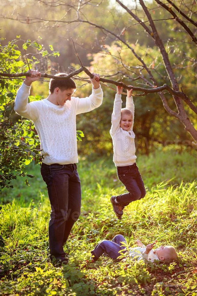pappa hjälper till att stödja pojken som hänger på trädgren, foto