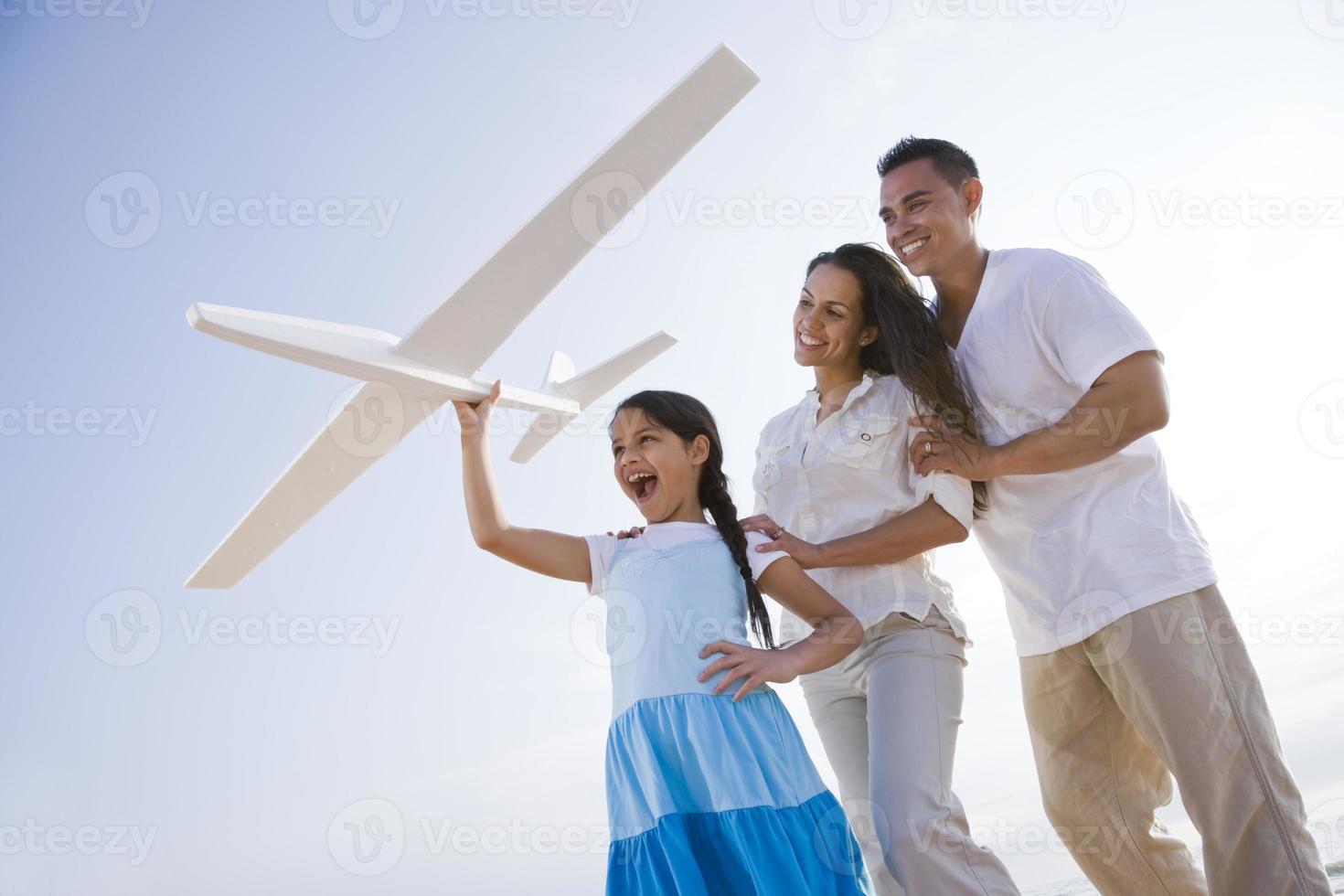 latinamerikansk familj och flicka som har kul med leksaksplanet foto