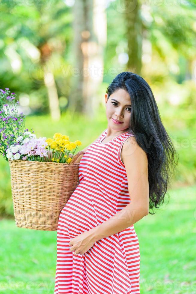 glad gravid kvinna picknick i parken foto