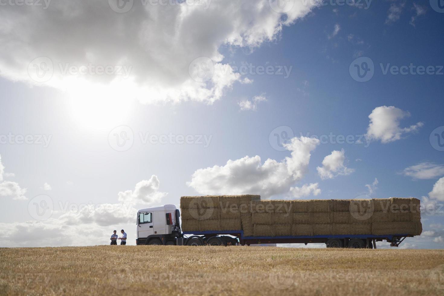 halmbalar på släpvagnen i soligt, lantligt fält foto