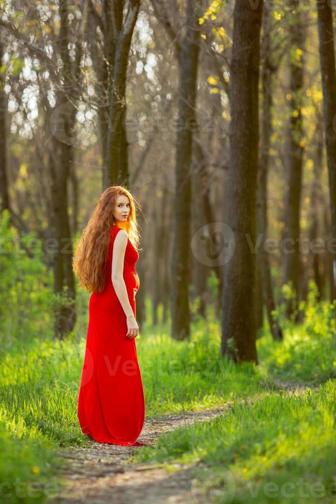 ung gravid kvinna som kopplar av och njuter av livet i naturen foto