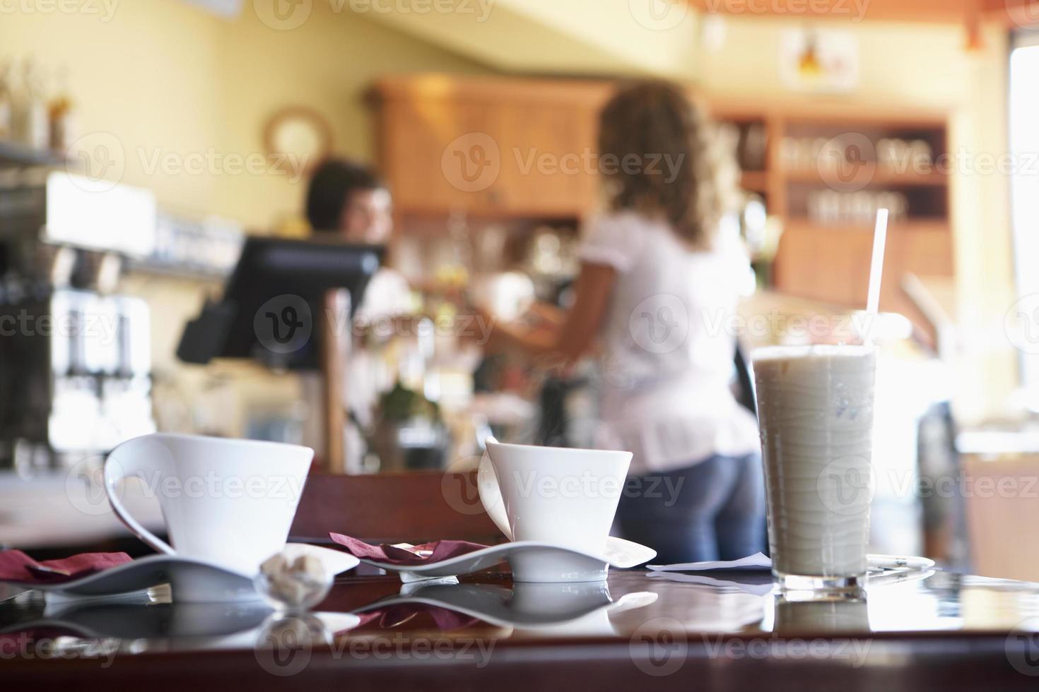 servitris som betjänar kvinnlig kund i cafŽ foto