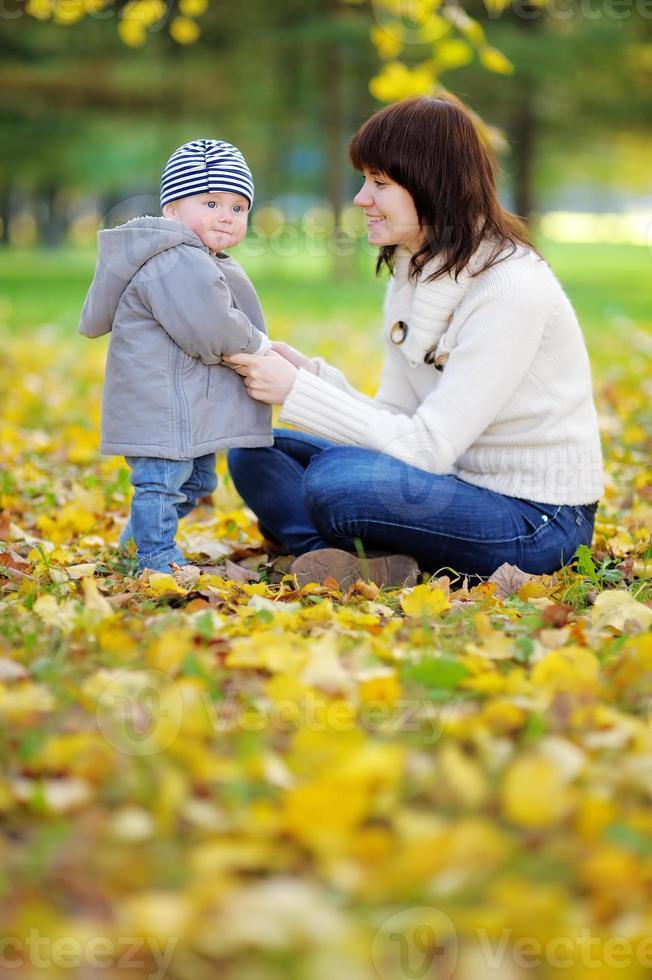 ung mamma med sin lilla bebis i höstparken foto
