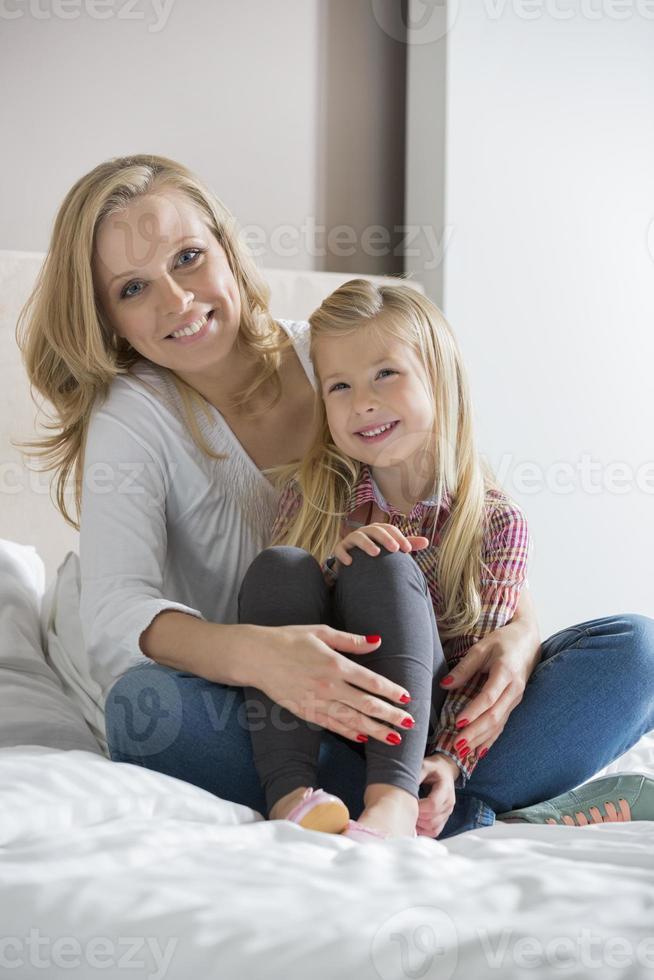 porträtt av glad mamma och dotter som sitter på sängen foto