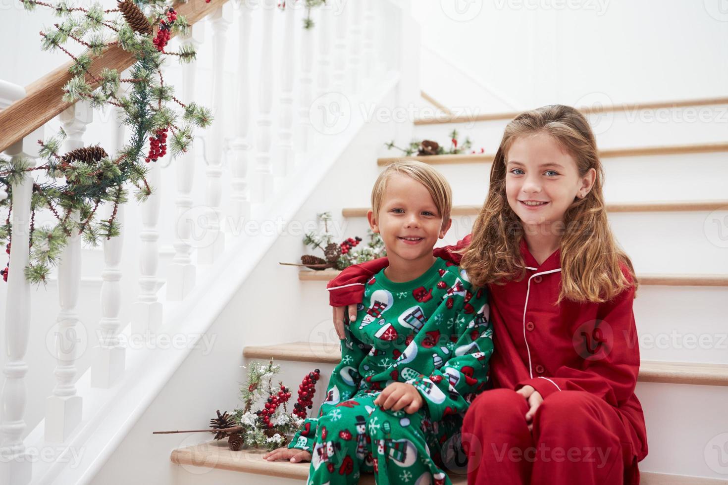 två barn som sitter på trappan i pyjamas vid jul foto