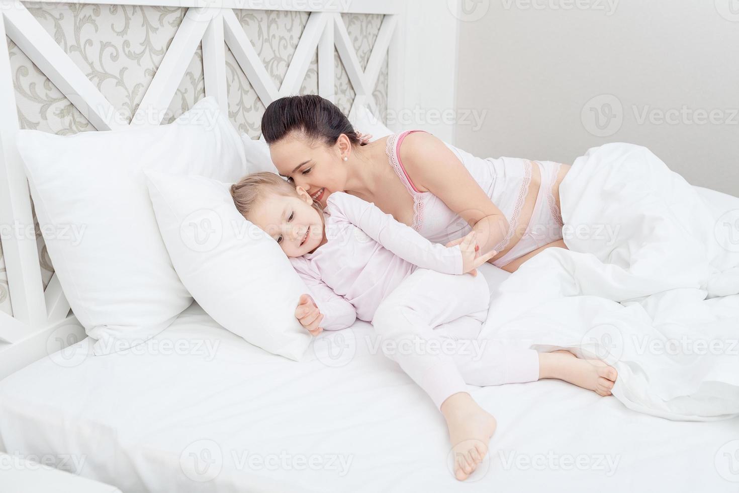 mamma och dotter i sängen foto