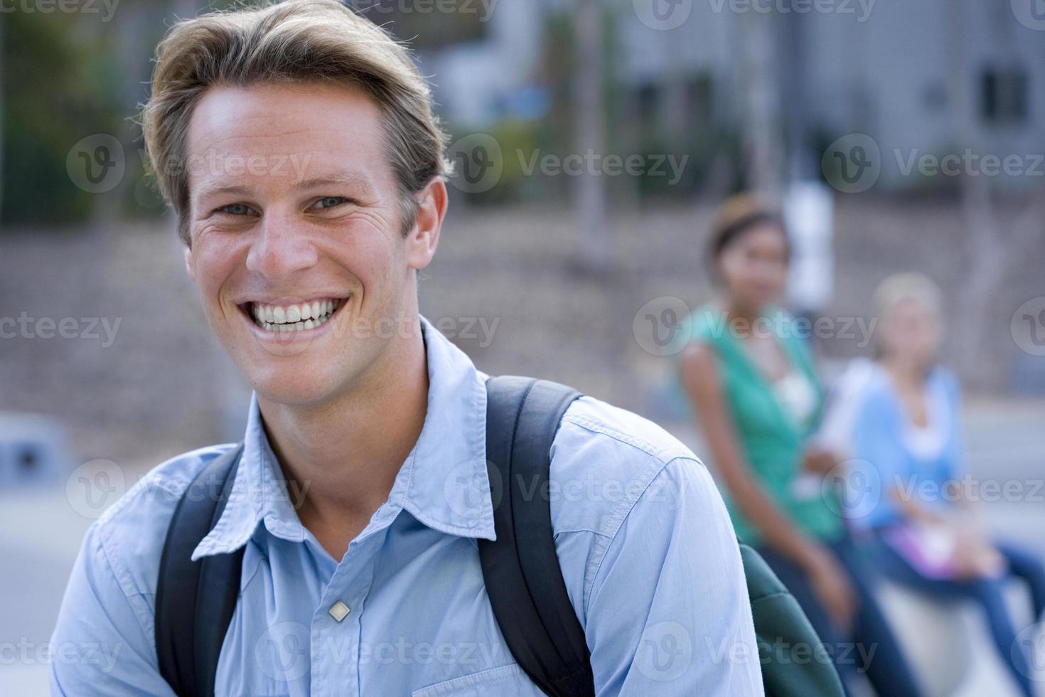 tonårspojke (16-18) som bär ryggsäck, ler, stående foto