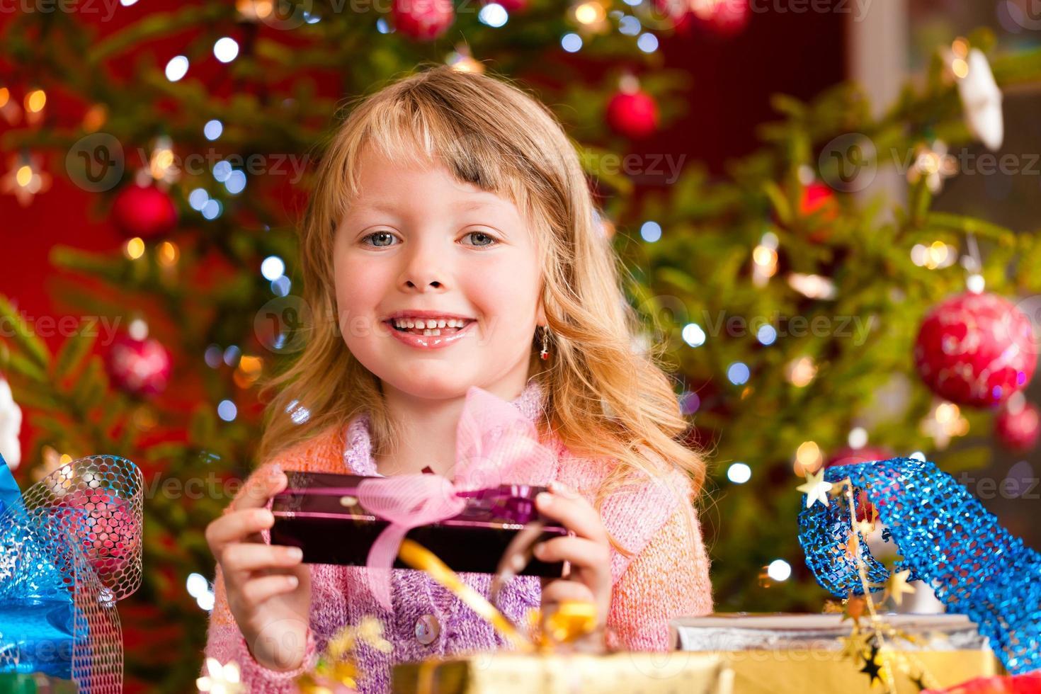 jul - liten flicka med julklapp foto