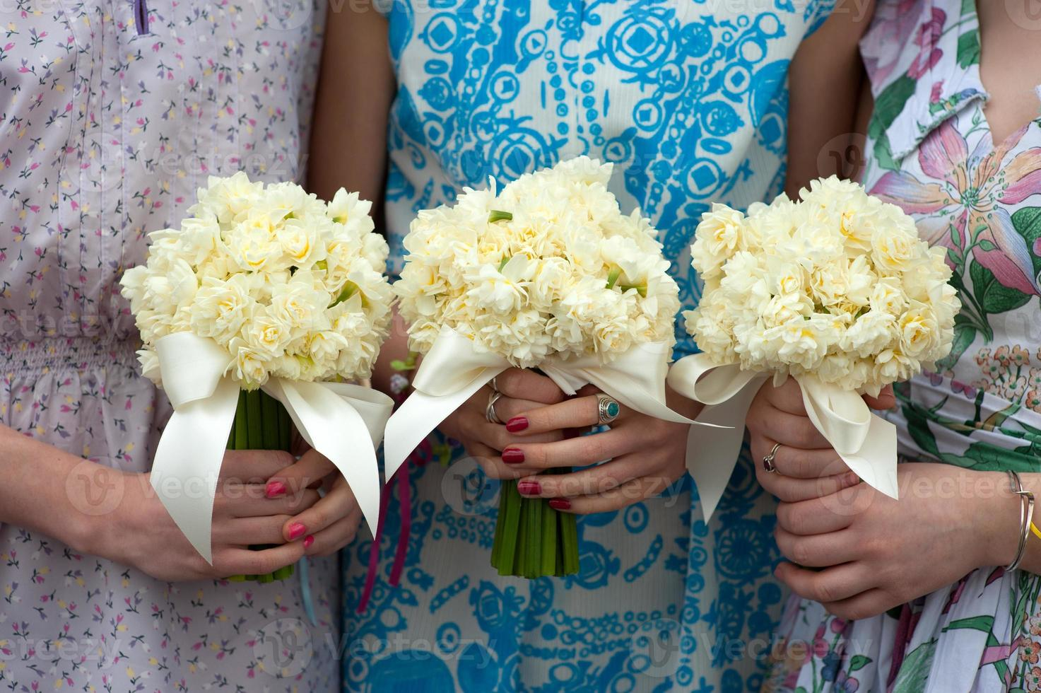 tre påsklilja bröllop buketter som innehas av brudtärnor foto