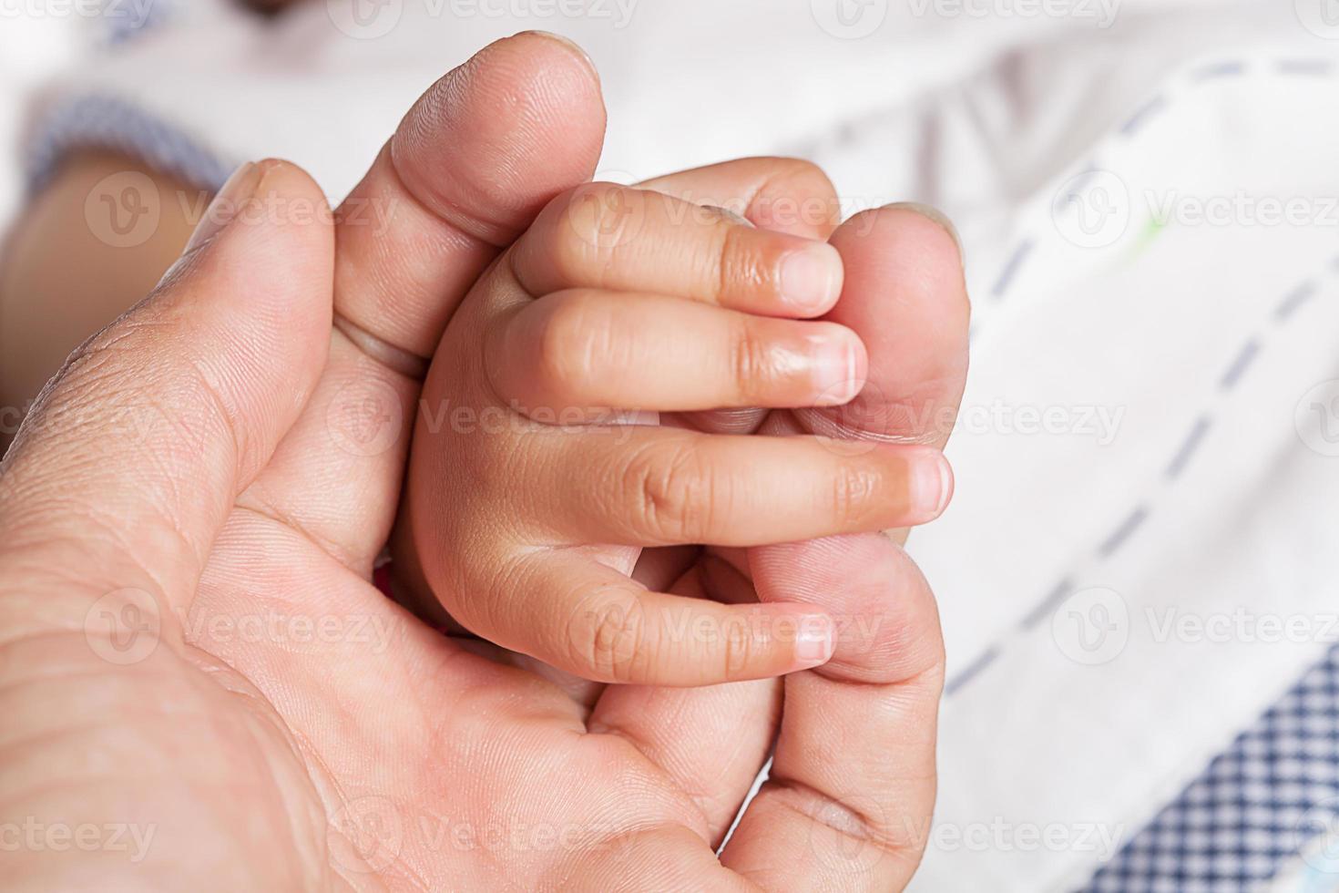 hand, finger far och baby dotter på 5 månader. foto