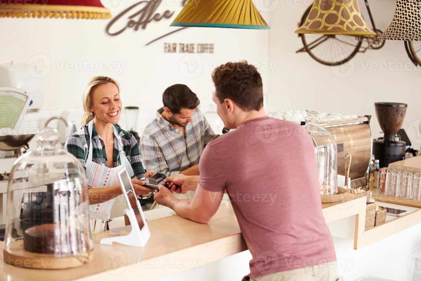 ung man betalar för sin beställning på ett kafé foto