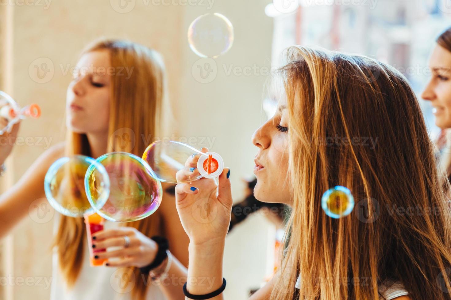 grupp med tre vänner som leker med såpbubblor foto