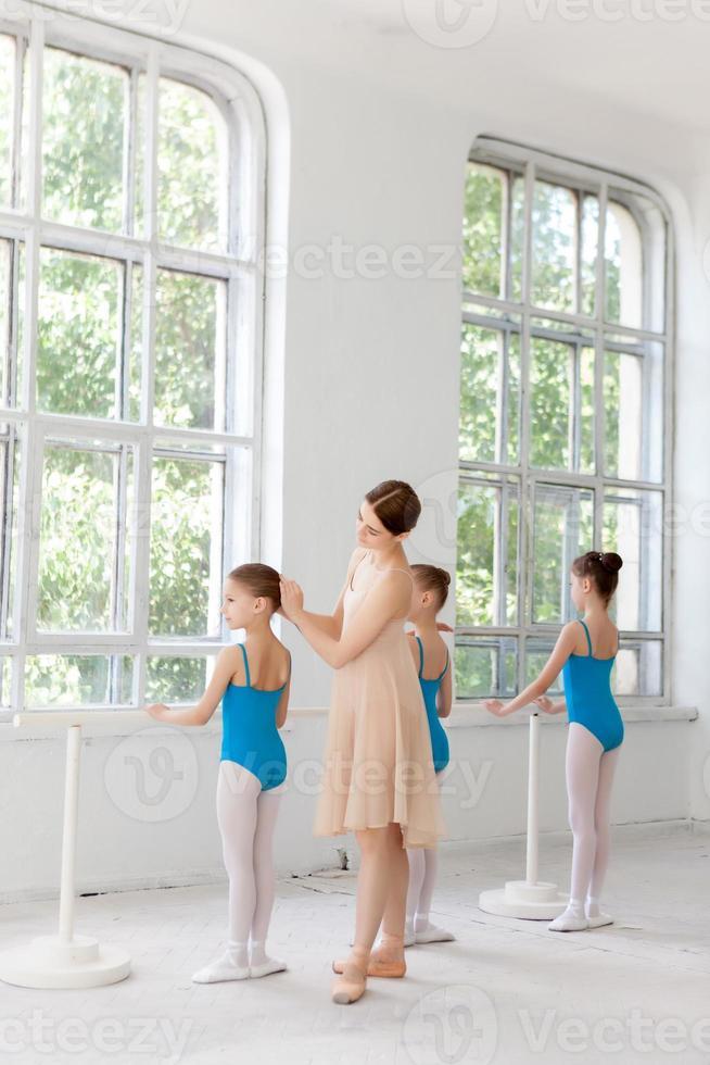 tre små ballerinor som dansar med personlig balettlärare i dans foto
