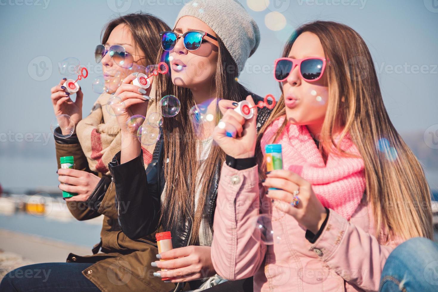 flickvänner som blåser såpbubblor foto