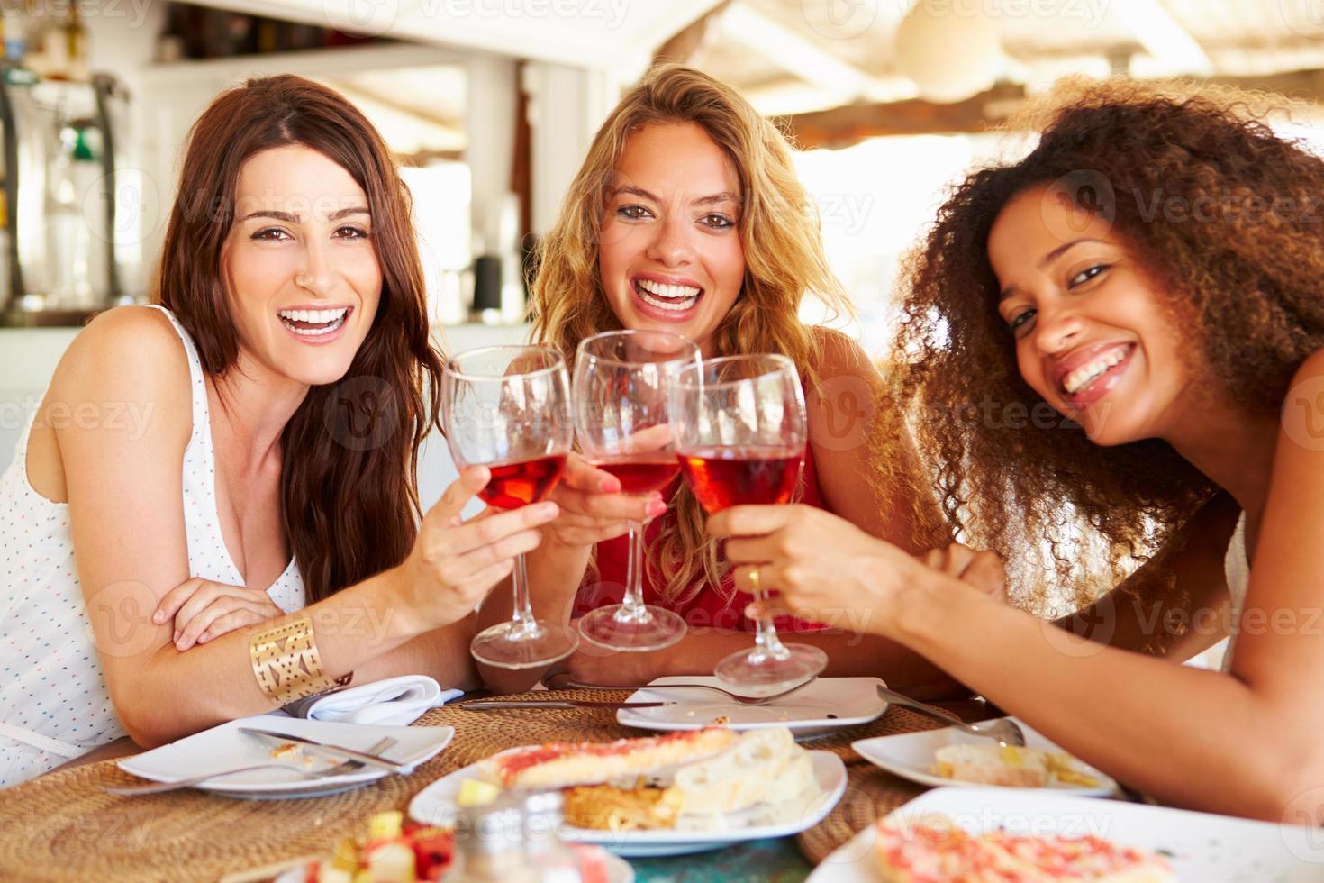 grupp kvinnliga vänner som tycker om måltid i utomhusrestaurangen foto