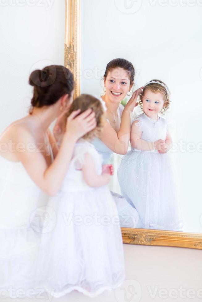vacker mor och bedårande småbarnsdotter som försöker på vita klänningar foto